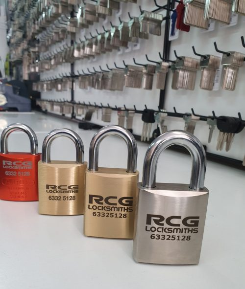 Four padlocks on the bench with the name RCG Locksmiths on each. A large amount of keys on a keyboard in the background.
